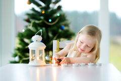 Beautiful little girl lighting a candle in white lantern Stock Photos