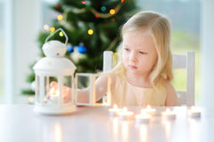 Beautiful little girl lighting a candle in white lantern Royalty Free Stock Photos