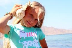 Beautiful little girl listening seashell. On beach Stock Images