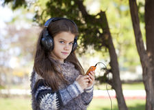 Beautiful little girl listening to music on headphones Stock Photography