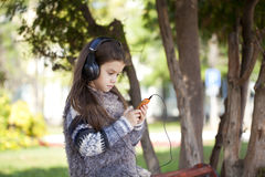 Beautiful little girl listening to music on headphones Royalty Free Stock Image