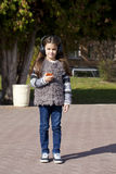 Beautiful little girl listening to music on headphones. In autumn park Royalty Free Stock Images