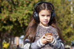 Beautiful little girl listening to music on headphones. In autumn park Stock Photos
