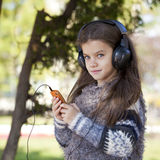Beautiful little girl listening to music on headphones. In autumn park Royalty Free Stock Photo