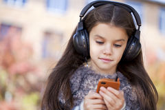 Beautiful little girl listening to music on headphones. In autumn park Stock Images