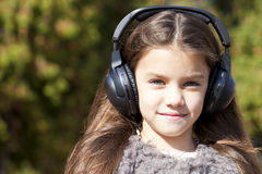 Beautiful little girl listening to music on headphones Stock Image