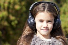 Beautiful little girl listening to music on headphones. In autumn park Stock Image