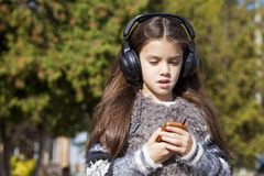 Beautiful little girl listening to music on headphones Stock Photos