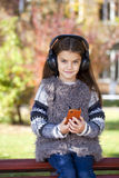 Beautiful little girl listening to music on headphones Royalty Free Stock Photos