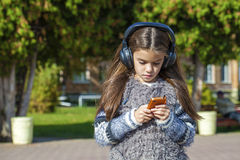 Beautiful little girl listening to music on headphones. In autumn park Royalty Free Stock Image