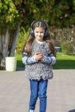 Beautiful little girl listening to music on headphones. In autumn park Stock Photo