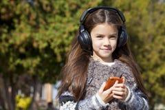Beautiful Little Girl Listening To Music On Headphones Stock Image