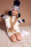 Beautiful little girl with long blond hair in cozy knitted clothes Royalty Free Stock Image