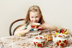 A beautiful little girl with long blond hair sitting at a table stock image