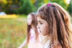 Beautiful little girl with long curly hair, looking worried at s. Unny summer day. Place for text Stock Photo