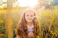 Beautiful little girl with long hair and smile in the summertime in the sunset park. Posing and looking at camera and smiling Stock Images