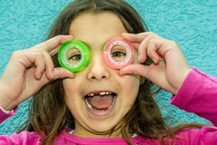 Beautiful little girl is looking through the circles of a scotch Stock Image