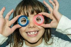 Beautiful little girl is looking through the circles of a scotch Royalty Free Stock Photography