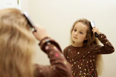 Cute little girl brushing hair while looking in the mirror Stock Photos
