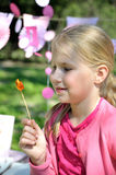 Beautiful little girl looking at a lollipop. Cute blonde toddler girl eating lollipop sitting in the park on a sunny summer day Royalty Free Stock Photo