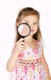 Beautiful little girl looking through a magnifying glass Royalty Free Stock Images