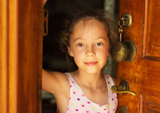 Beautiful little girl looking out of the door. Royalty Free Stock Photography