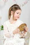 A beautiful little girl looking to small mirror Royalty Free Stock Photography