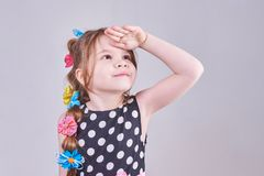 A beautiful little girl looks up, putting her hand to her forehead stock images