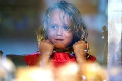 Beautiful little girl looks in the window of a shop in OIA, and makes funny faces royalty free stock photography