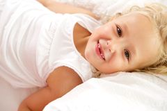 Beautiful little girl lying on bed. Close up portrait of beautiful little girl lying on bed royalty free stock photo