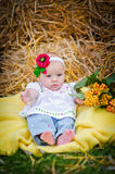 Beautiful little girl lying on a blanket in the hay Stock Photography
