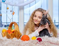 Beautiful little girl lying on carpet and playing with bunny. Royalty Free Stock Images