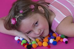 Beautiful little girl lying down on colorful pom poms Royalty Free Stock Image