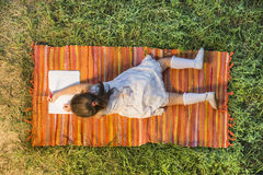 Beautiful little girl lying down on the picnic blanket drawing. Outside in backyard playground, seen from above Royalty Free Stock Photo