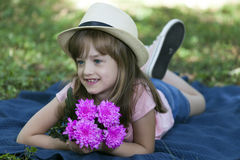 Beautiful little girl lying on the grass and enjoy Royalty Free Stock Image