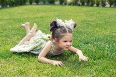 Beautiful little girl lying on the grass stock images