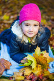 Beautiful little girl with maple leaves lying in autumn park Stock Images