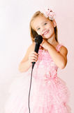 Beautiful little girl with microphone in princess dress Stock Photo