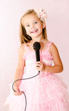 Beautiful little girl with microphone Royalty Free Stock Photography