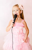 Beautiful little girl with microphone Stock Images