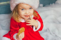 Cute little girl in Santa hat with cookies at home. Beautiful little girl with milk and cookies for Santa Claus in festively decorated room Royalty Free Stock Images