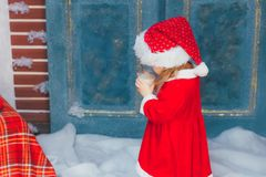 The girl drinks milk in a Santa Claus costume. Beautiful little girl with milk for Santa Claus in festively decorated room Stock Photography