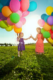 Beautiful little girl with mother colored balloons and rainbow u Stock Photography