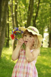 Beautiful little girl on nature with a bouquet of flowers Stock Image