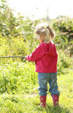 Beautiful little girl in nature playing with a stick Stock Photography