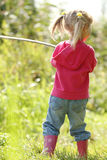 Beautiful little girl in nature playing with a stick Royalty Free Stock Photography