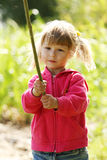 Beautiful little girl in nature playing with a stick Stock Image
