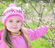 Beautiful little girl near a flowering tree Royalty Free Stock Images