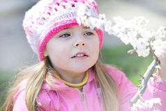 Beautiful little girl near a flowering tree Royalty Free Stock Photo