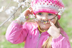 Beautiful little girl near a flowering tree Royalty Free Stock Image